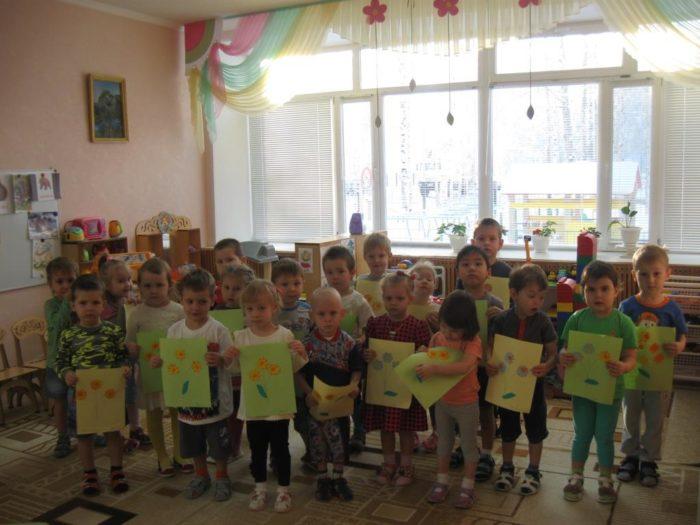 Дети в саду стоят с рисунками