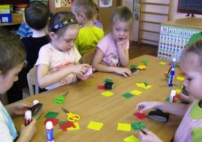 Дети вырезают детали из цветной бумаги