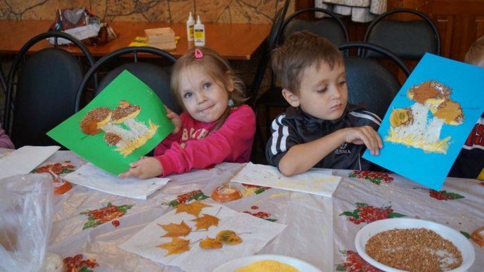 Девочка и мальчик показывают свои аппликации с грибами