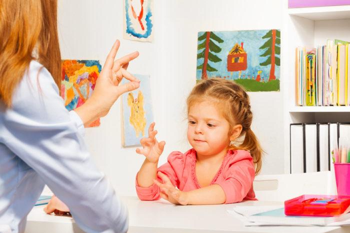 Девочка повторяет «собачку» вслед за учительницей