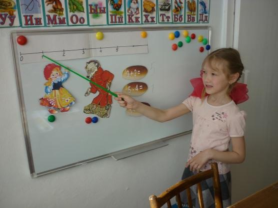 Девочка у доски показывает на отрезке фигурки