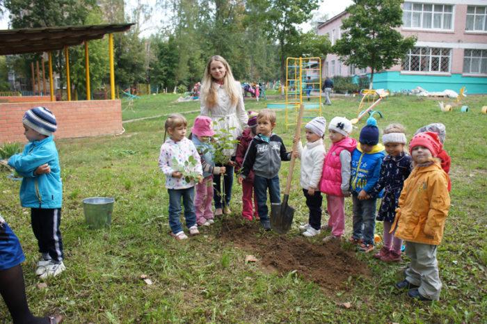 Группа малышей с воспитательницей на улице