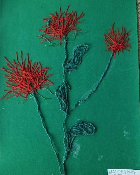 Красные цветочки на зелёном листе бумаги с технике ниткопись