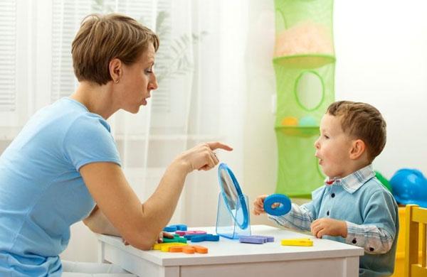 Мальчик перед зеркалом произносит звук «о», логопед указывает пальцем