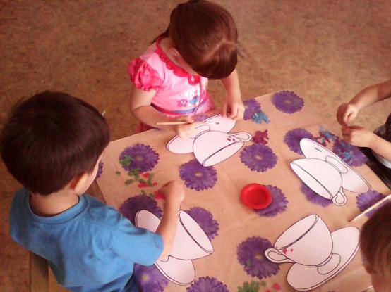 Мальчик с иней футболке и девочка в розовом платье ставят точки на чайную пару, видны руки ещё 2 детей