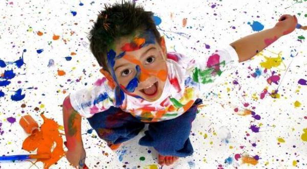 Мальчик в пятнах от краски, смеётся