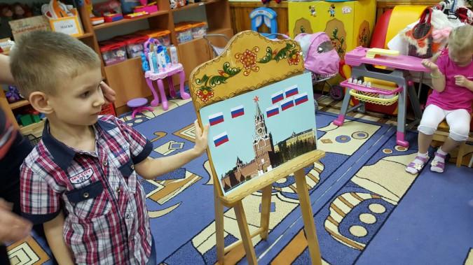 Мальчик в рубашке в клетку у проекта с нарисованным Кремлём