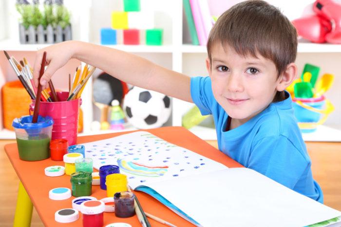Мальчик в синей футболке перед открытым альбомом, набор карандашей. гуашь на столе