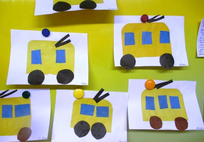 Несколько бумажных жёлтых троллейбусов с синими окнами