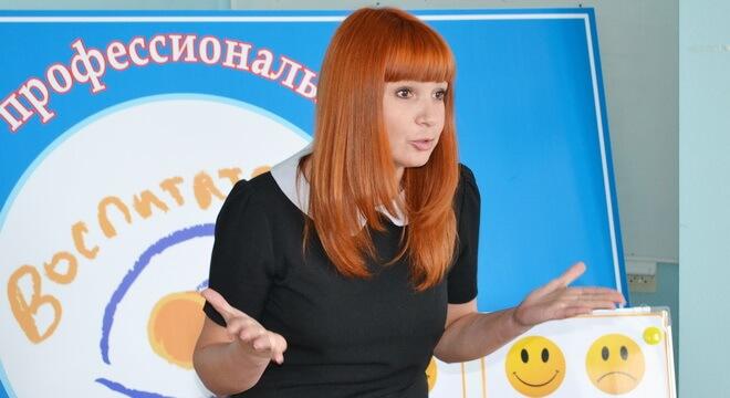 Рыжая девушка на фоне логотипа «Воспитатель года»