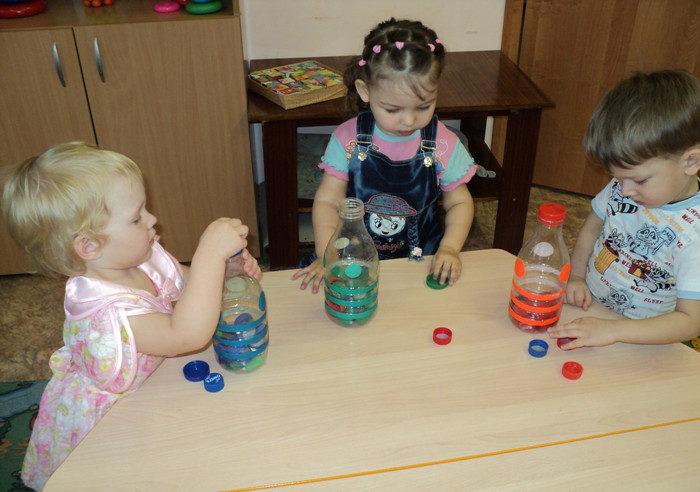 Трое детей складывают небольшие крышечки в пластиковые бутылки