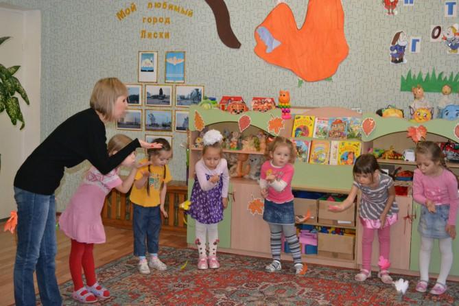 Воспитатель проводит пальчиковую гимнастику на коврике, на заднем фоне книги, рисунки, надпись: мой любимый город лиски