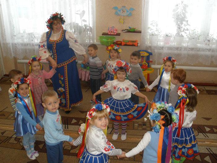 Воспитательница и дети в костюмах ведут хоровод