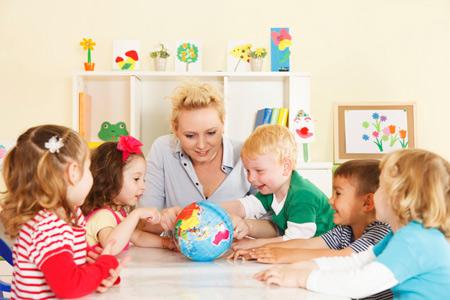 Воспитательница и дети за столом рассматривают глобус