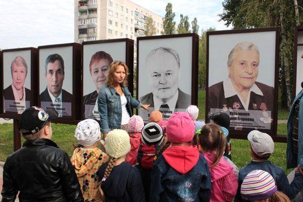 Воспитательница на фоне портретов известных жителей города рассказывает что-то детям