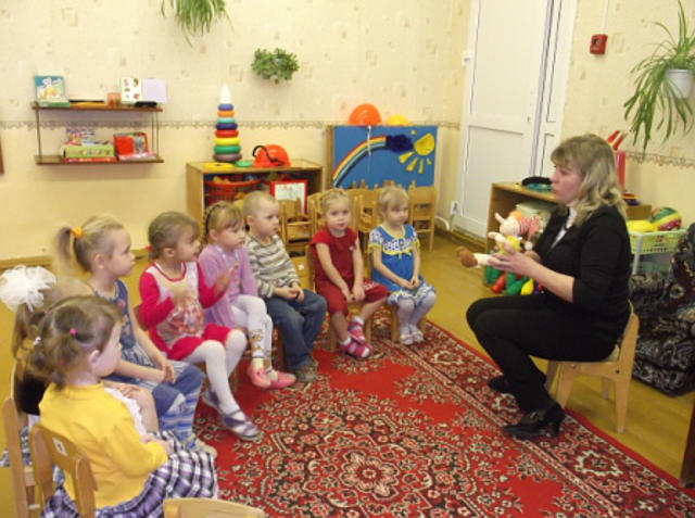 Воспитательница показывает группе игрушку Буратино