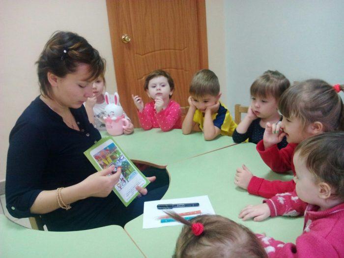 Воспитательница показывает картинки в книжке
