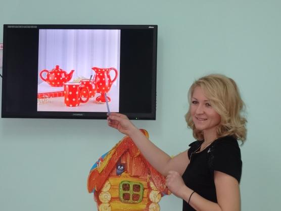 Воспитательница показывает на экране красный сервиз в горошек, под доской рисунок домика