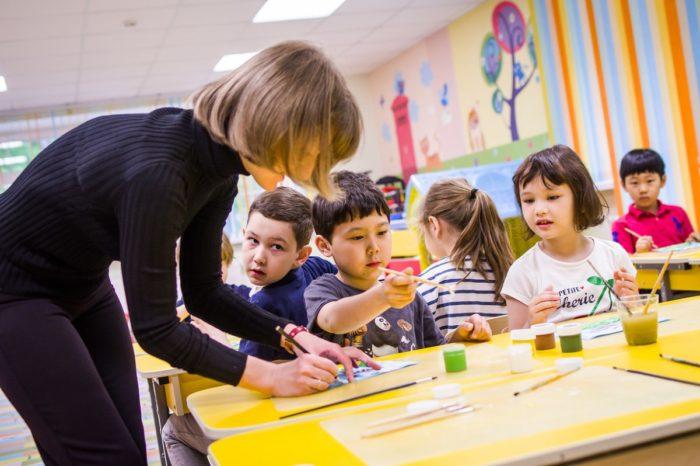Воспитательница помогает детям рисовать