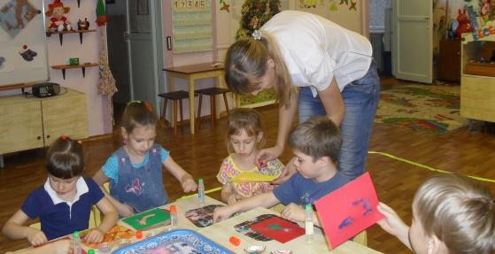 Воспитательница помогает детям с аппликацией