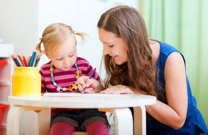 Воспитательница рисует с девочкой в полосатом свитере