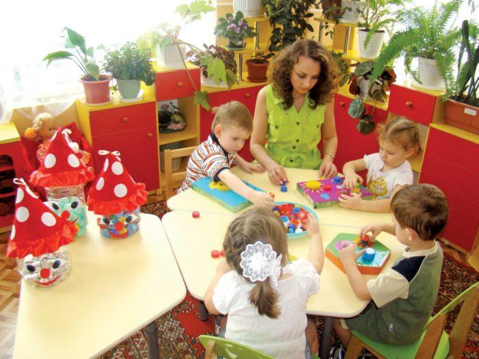 Воспитательница с детьми за круглым столом складывают конструктор