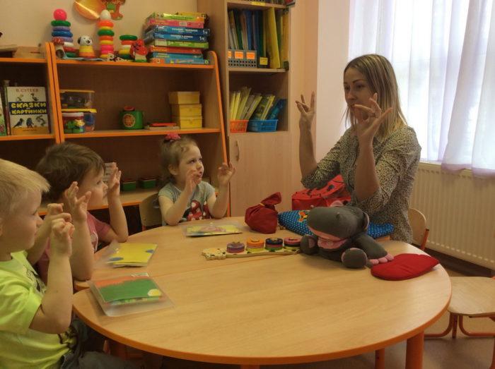Воспитательница с детьми за круглым столом занимаются пальчиковой гимнастикой
