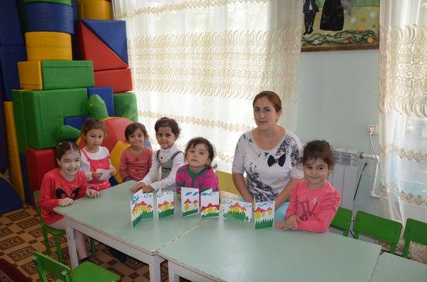 Воспитательница с детьми за столом, дети держат аппликации «Грибы»