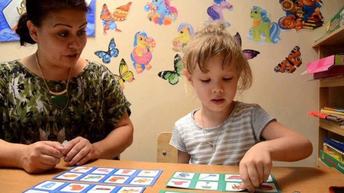 Воспитательница с девочкой играют в лото