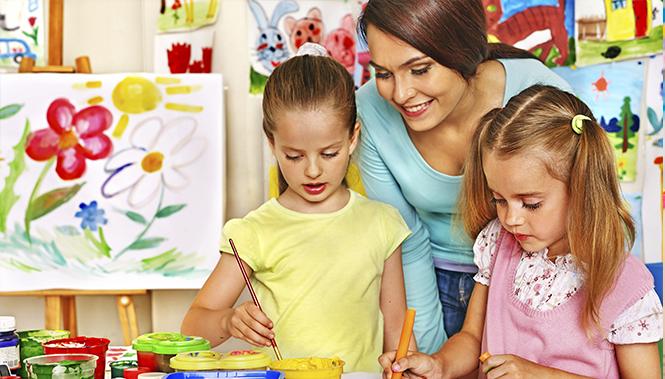 Воспитательница с двумя девочками рисуют