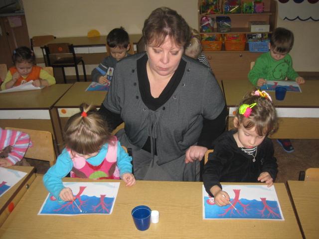 Воспитательница сидит между двумя девочками, рисующими ватными палочками