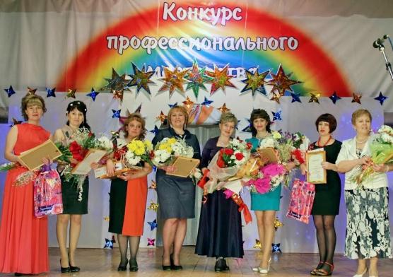 Воспитательницы стоят на сцене, на заднике радуга и подпись: «Конкурс профессионального»