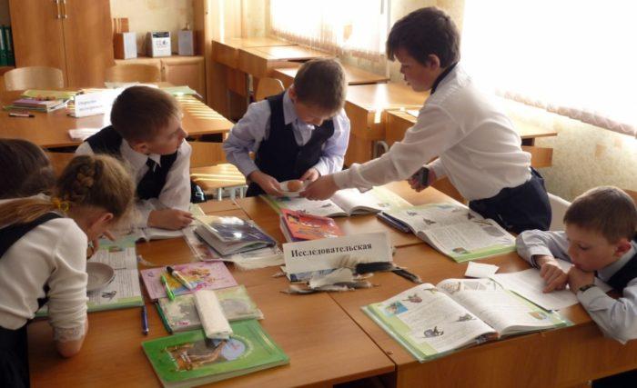 6 ребят за сдвинутыми 2 партами, на столе табличка — исследовательская