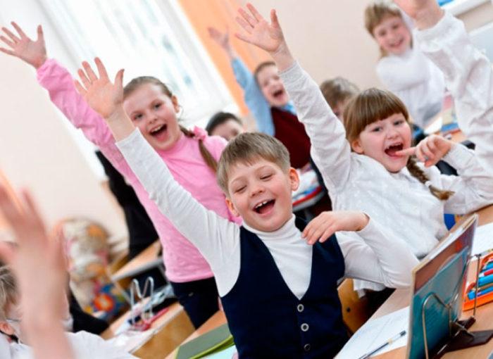 Дети тянут руки для ответа, на переднем плане мальчик, на заднем — девочка в розовой водолазке