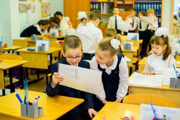 Дети за жёлтыми партами что-то обсуждают, у мальчика в очках и девочки в руках лист в файле