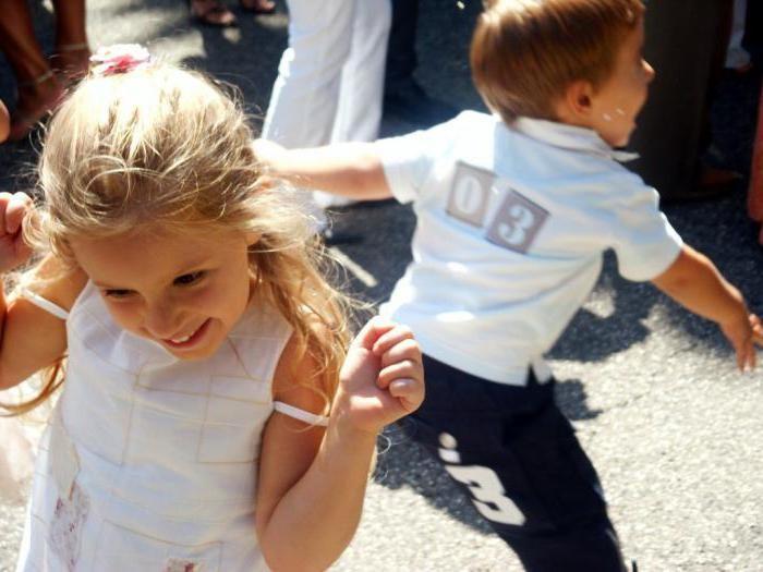 Девочка в белой кофточке, мальчик сзади кричит, расставив руки