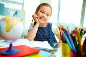Девочка в джинсовом сарафане и белой футболке улыбается, приложив руку с карандашом к щеке, на переднем плане глобус, карандаши