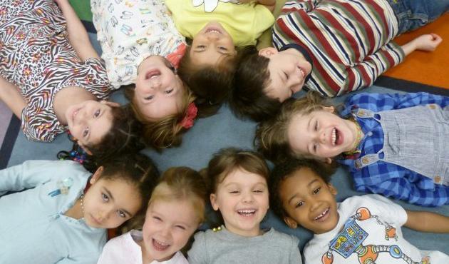 Дети лежат, соприкасаясь головами, смеются