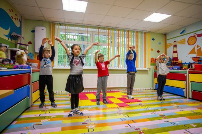 Дети с поднятыми руками выполняют упражнение в комнате