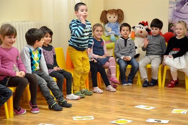 Дети сидят полукругом, мальчик что-то выкрикивает стоя