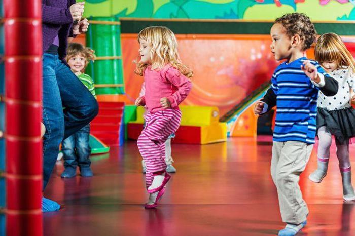Дети, взявшись на руки, танцуют на сцене перед родителями