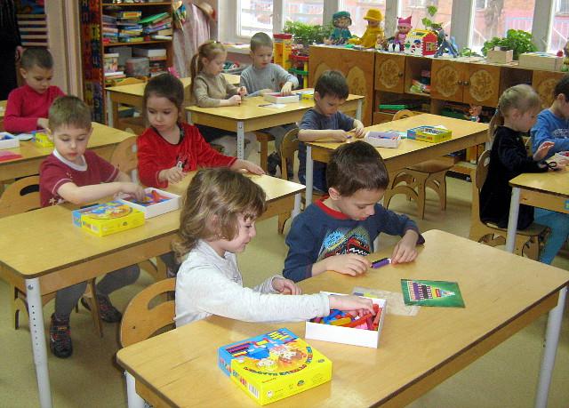 Дети за столиками лепят
