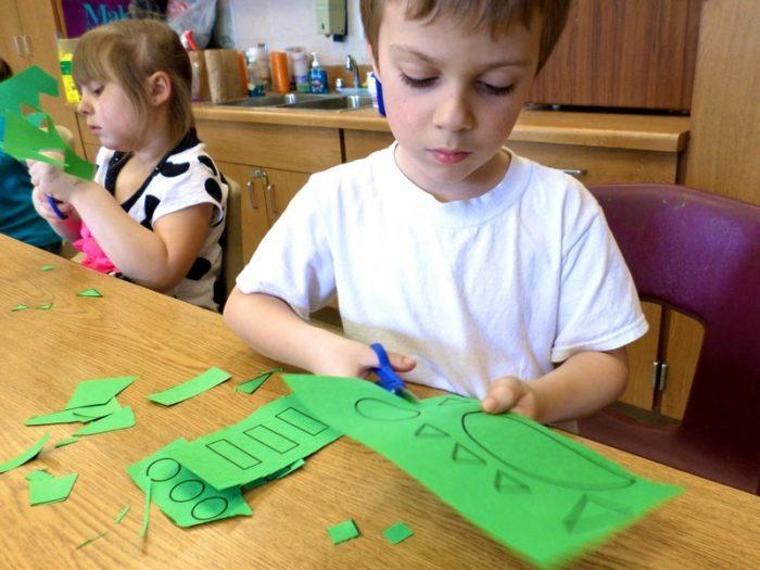 Мальчик и девочка на заднем фоне режут детали из зелёной бумаги