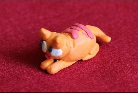 Оранжевый кот с розовыми полосками на спине лежит