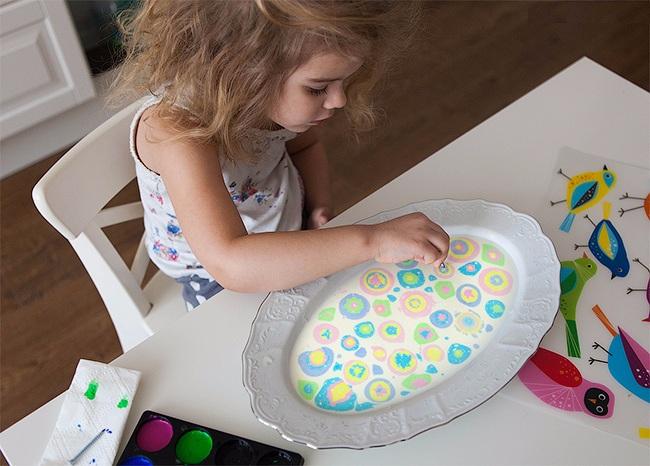 Ребенок рисует красками на жидкой поверхности