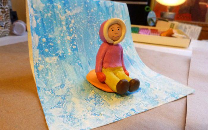 Ребёнок в розовой курочке сидит на ледянке