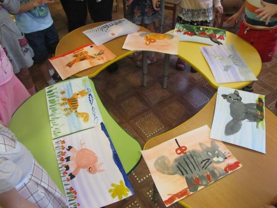 Рисунки детей лежат по кругу, дети стоят позади столов