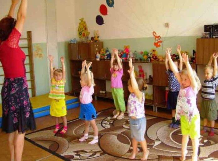 Воспитатель проводит занятие ритмопластикой с детьми