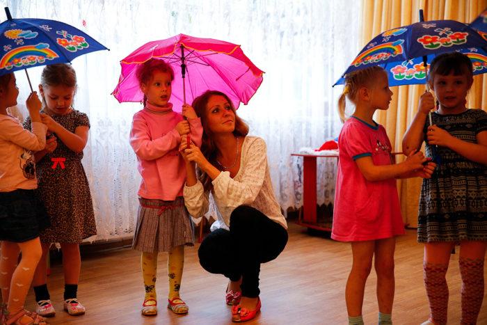 Воспитательница и дети по двое под зонтиками