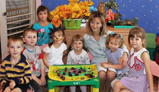 Воспитательница с детьми сидит за столом, одна девочка в шапочке с иголками ёжика